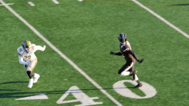 ms ts professional football wide receiver running down sideline covered by defensive back and missing pass - 失敗点の映像素材/bロール