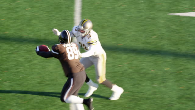 stockvideo's en b-roll-footage met ms ts professional football wide receiver running down sideline covered by defensive back and catching pass - sportwedstrijd