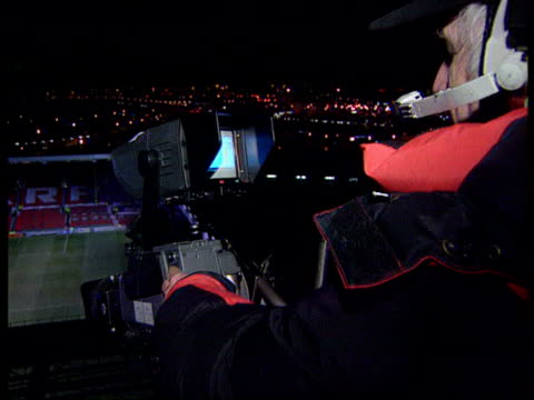 vídeos de stock, filmes e b-roll de professional footballers threaten strike lib cameraman pointing camera at football pitch int crew and commentators in tv control room overlooking... - comentarista