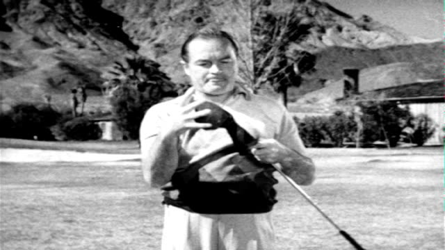 professional golfer lloyd usa mangrum teeing off, comedian bob hope inframe bending over, ben hogan looking , bob hope motioning mangrum move, bob... - ボブ ホープ点の映像素材/bロール