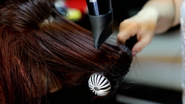 Professional hairdresser using hairdryer
