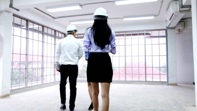 Professional jobs,engineer talking and looking at building plans in construction site.