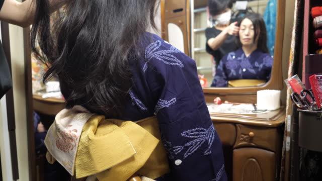 professional kimono dresser making up hair in fitting room - yukata robe stock videos & royalty-free footage