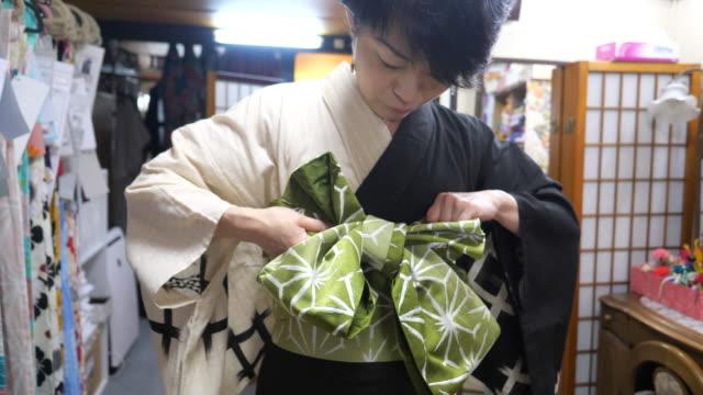professionelle kimono kommode binden obi schärpe für sich selbst in der umkleidekabine - kommode stock-videos und b-roll-filmmaterial