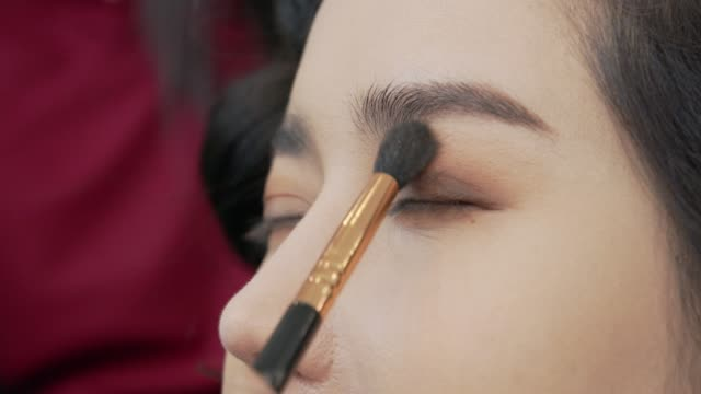 professional make up and cosmetic brush near her eye on the close up shot