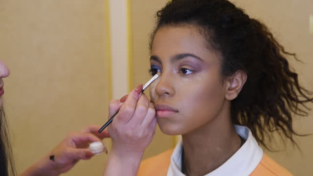 professional make-up artist makes make-up for attractive afro-american model. beauty and fashion concept. - beauty spa stock videos & royalty-free footage