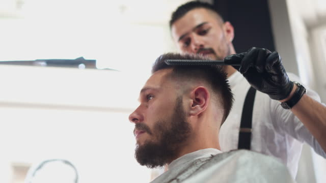 professional male hairdresser giving haircut - barber chair stock videos & royalty-free footage