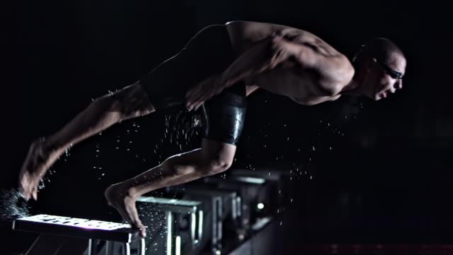 vídeos de stock, filmes e b-roll de professional male jumping off the starting block - kranj