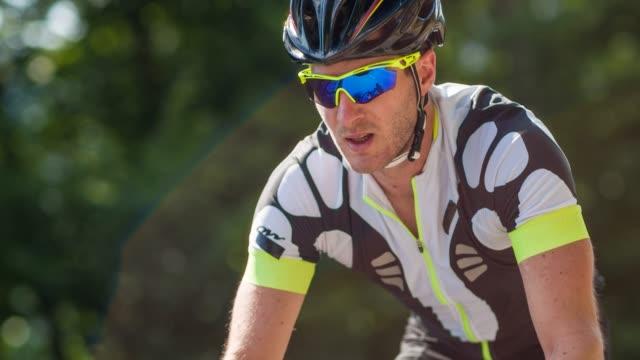 professional male road cyclist riding uphill - sforzo video stock e b–roll