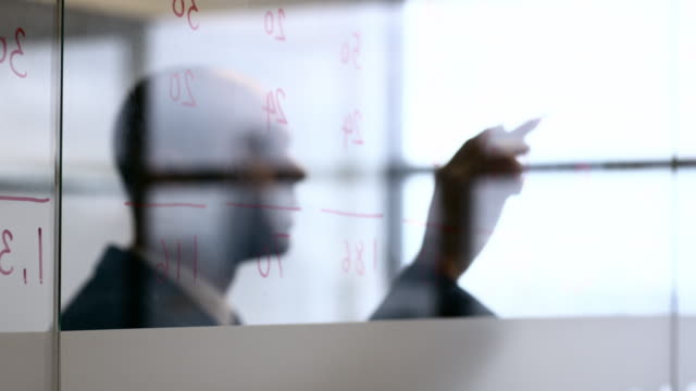 A professional man writing numbers on glass in an office environment