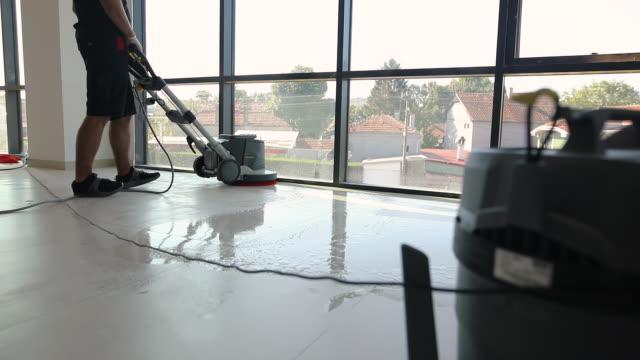 vídeos y material grabado en eventos de stock de trabajadores manuales profesionales limpiando el piso juntos como un equipo - piso de edificio