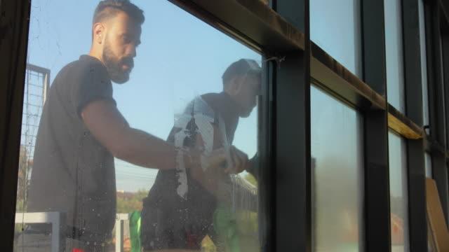 stockvideo's en b-roll-footage met professionele handarbeiders die aan het wassen van vensters samen werken - dienstverlener