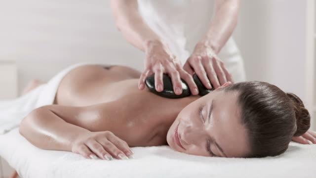 hd: professional massage with stones - massage table bildbanksvideor och videomaterial från bakom kulisserna