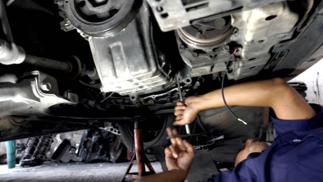 vídeos y material grabado en eventos de stock de mecánico profesional reparación de un coche en el taller de reparación de automóviles - mecánico de coches