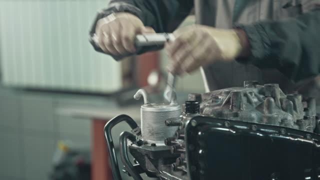 professional mechanic repairing a car in auto repair shop - laboratorio riparazioni video stock e b–roll