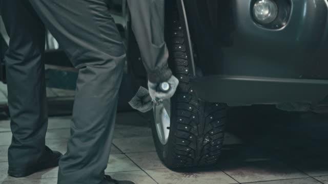 vídeos de stock, filmes e b-roll de mecânico profissional consertando um carro em oficina de reparação automóvel - tyre