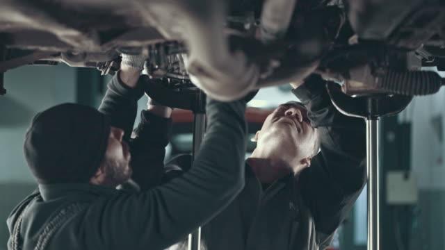 vidéos et rushes de mécanicien professionnel, réparer une voiture dans l'atelier de réparation automobile - moteur
