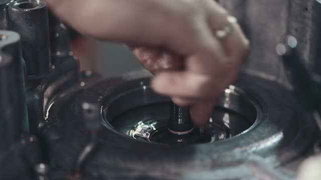 vídeos de stock, filmes e b-roll de mecânico profissional consertando um carro em oficina de reparação automóvel - óleo de motor
