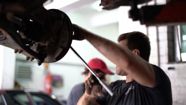 professional mechanic repairing a car in auto repair shop - mechanic stock videos & royalty-free footage