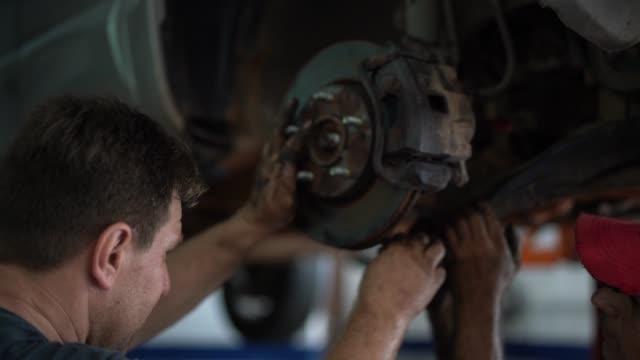 vídeos de stock, filmes e b-roll de mecânico profissional consertando um carro em oficina de reparação automóvel - mecânico de carro