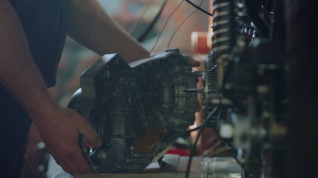 CU. Professional mechanic takes motorcycle apart in auto repair shop.