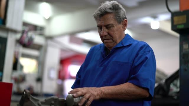 stockvideo's en b-roll-footage met professionele monteur, werken bij auto reparatiewerkplaats - small business - alleen één seniore man