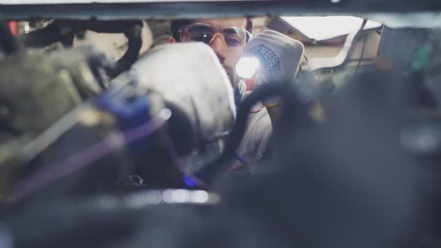 カーサービスで車両に取り組むプロのメカニック。 - 交代点の映像素材/bロール
