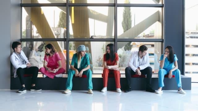 vidéos et rushes de professionnels médicaux professionnels attendant en ligne à l'hôpital - salle d'attente