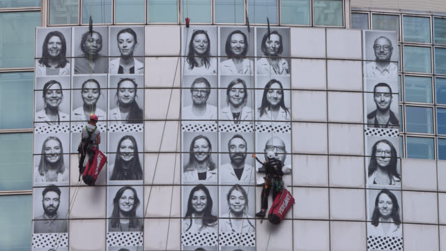 professional mountaineers install posters featuring portraits of health workers on the facade of the opera bastille on june 08, 2020 in paris,... - バスティーユ点の映像素材/bロール