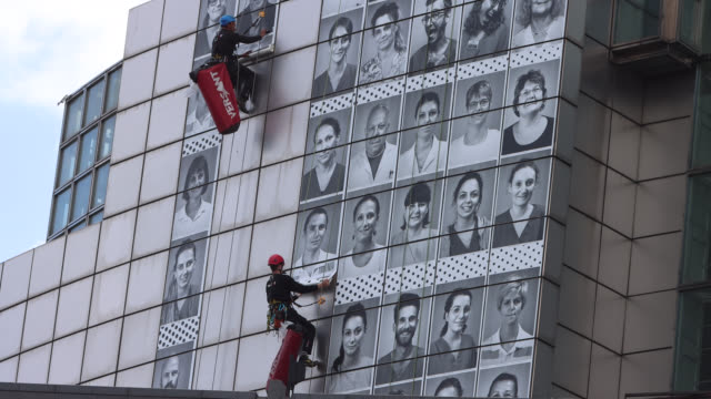 professional mountaineers install posters featuring portraits of health workers on the facade of the opera bastille on june 08 2020 in paris france... - bastille stock-videos und b-roll-filmmaterial