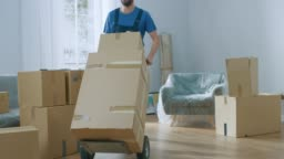 Professional Mover with Hand Truck Loads it With Cardboard Boxes and Helps People Move out and Relocate into the New House.