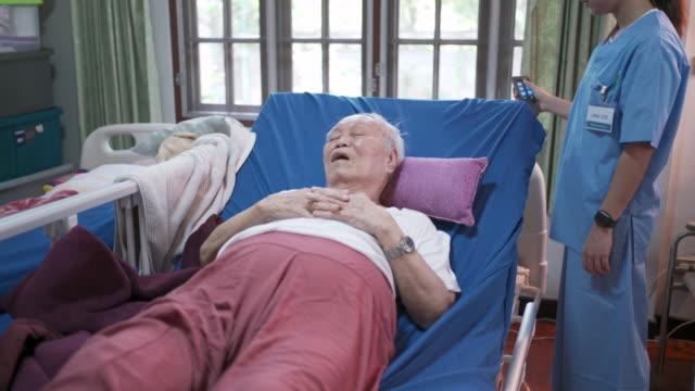 vidéos et rushes de infirmière professionnelle opérant le lit électrique pour le patient aîné - visite à domicile