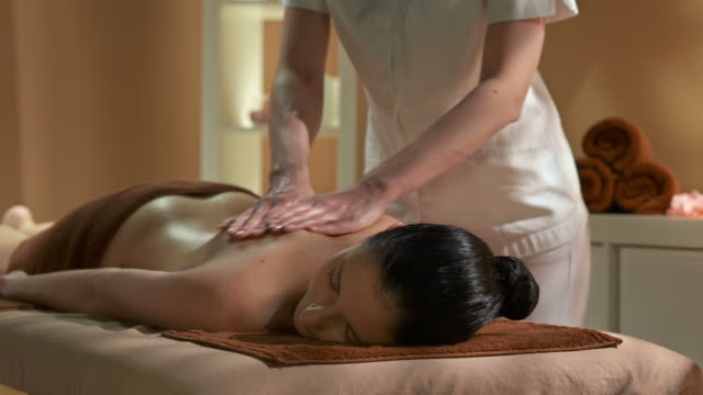 hd: professional oil massage in spa center - pampering stock videos & royalty-free footage