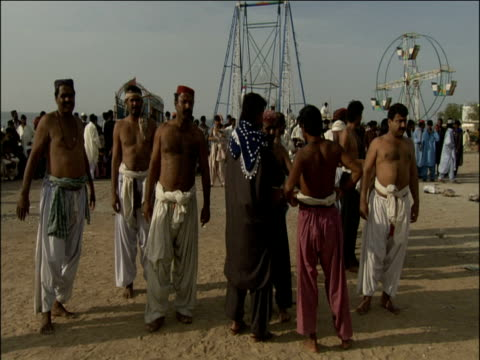 professional pahalwan wrestlers listen to radio announcer and limber up for impending competition pakistan - spielkandidat stock-videos und b-roll-filmmaterial