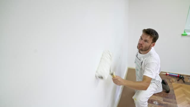 professional painter painting the wall white using a painting roller - wall building feature stock videos & royalty-free footage