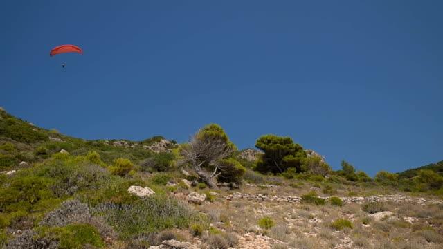 parapendio professionista nella perfetta giornata di sole che si esibisce contro il cielo blu soleggiato. - sunny video stock e b–roll