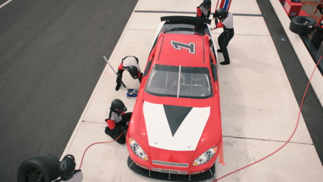 Professional pit crew lowers jack on stock car and gives the all clear for driver to return to race.