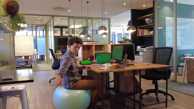 it professional programmer sitting on yoga ball zoom out with basketball slam dunk and throwing of ball - zoom out stock videos & royalty-free footage