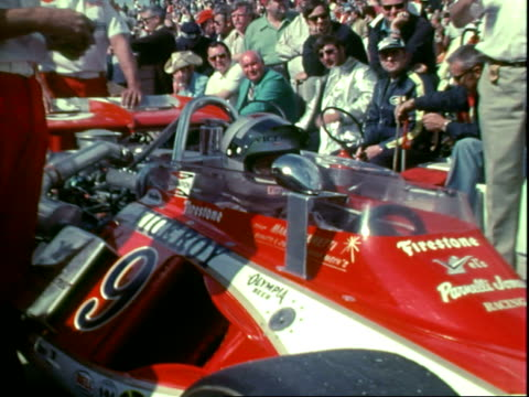 professional race car driver mario andretti squeezed behind wheel of formula one race car parked in pits at indianapolis 500 race / mario andretti's... - protective sportswear stock videos & royalty-free footage
