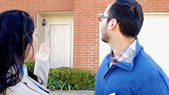 Professional real estate agent showing suburban home to Hispanic male home buyer