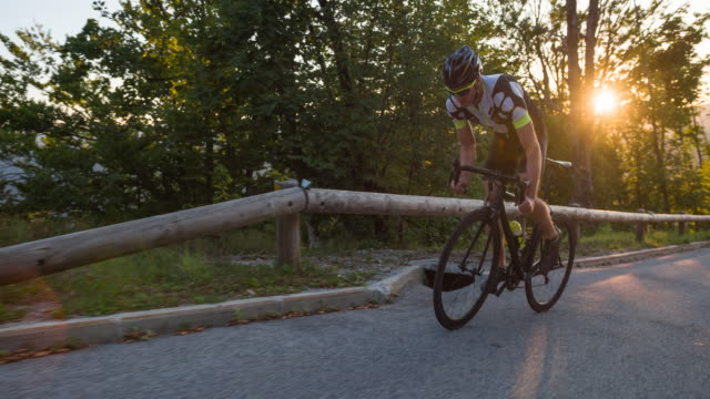 Professional road cyclist at the view of finish line cycling uphill with sunset in the background