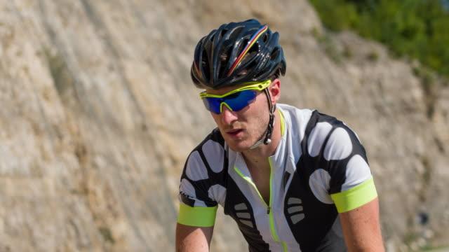 vídeos de stock, filmes e b-roll de ciclista de estrada profissional, andar de bicicleta ao lado de uma parede de montanha - colina acima