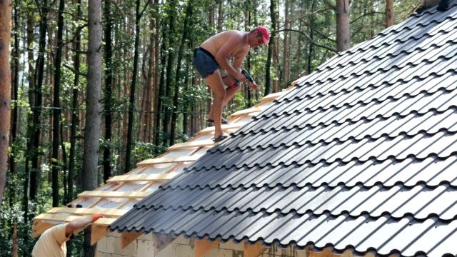 Professional roofer fixes the metal roofing material with screws.