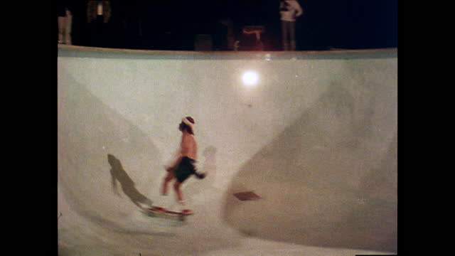 professional skateboarder, tony alva, and another skateboarder, skateboarding in an empty pool at a house party at night while people watch; 1978. - cool attitude stock videos & royalty-free footage