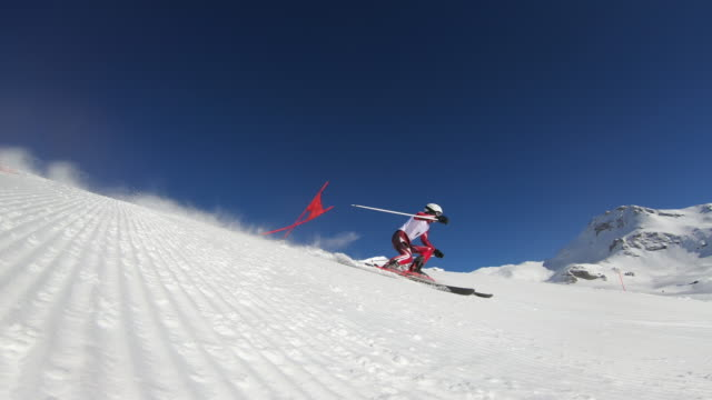 4k professional ski racer skiing one turn of giant slalom - competizione video stock e b–roll
