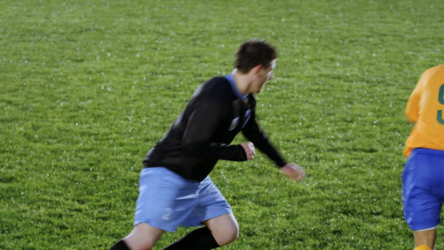 MS professional soccer player dribbling ball past opposing defender on field at night