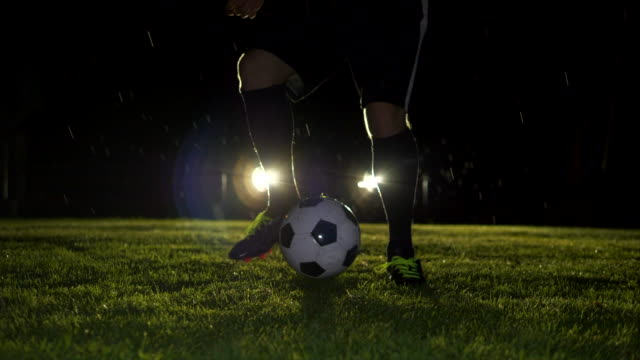 professional soccer player kicking ball on soccer field at night - ball video stock e b–roll