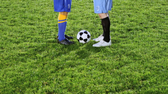 MS TU professional soccer players from opposing teams shaking hands over ball in center of field at night
