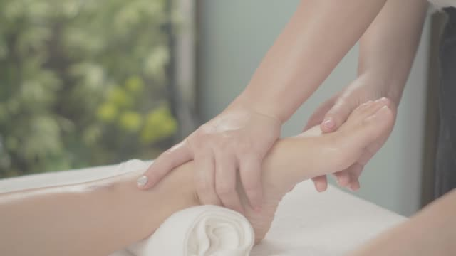 professional therapist giving traditional thai foot massage to a woman in spa - reflexology stock videos and b-roll footage