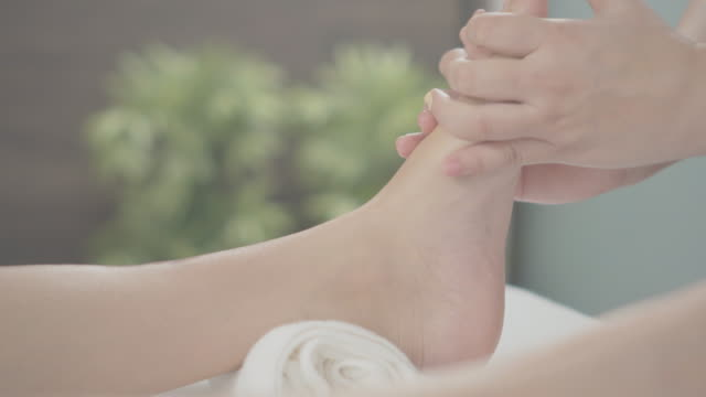 professional therapist giving traditional thai leg and foot massage to a woman in spa - reflexology stock videos and b-roll footage